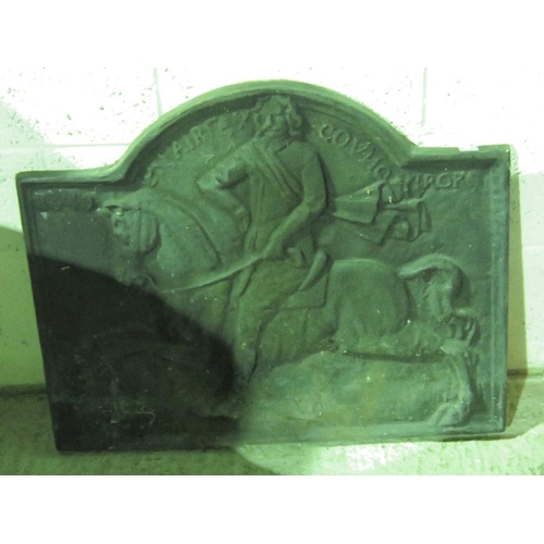 1149 - A heavy cast iron arch-top fire back with figure on a horse in relief decoration upon. 85cm x 69 max...