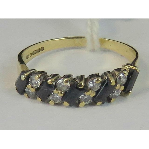 138 - A 9ct gold sapphire ring, five baguette cut sapphires separated by four pairs of white stones, all i...
