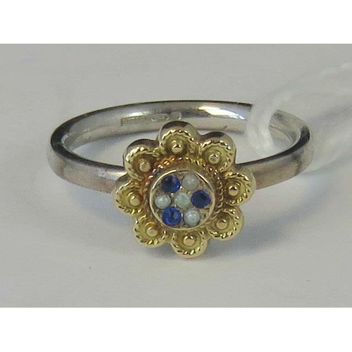 118 - A silver and yellow metal ring, yellow metal head set with sapphire chips and seed pearls on a white...