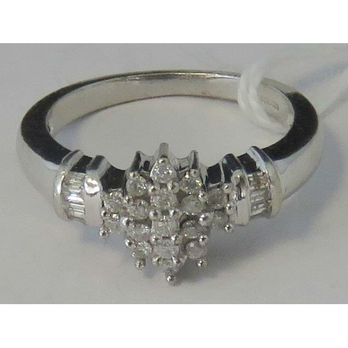 124 - A 9ct white gold and diamond cluster ring, central diamond shaped cluster flanked by baguette diamon...