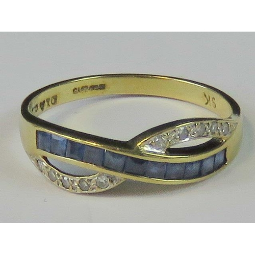 133 - A 9ct gold sapphire and diamond crossover design ring, a row of channel set square cut blue sapphire...