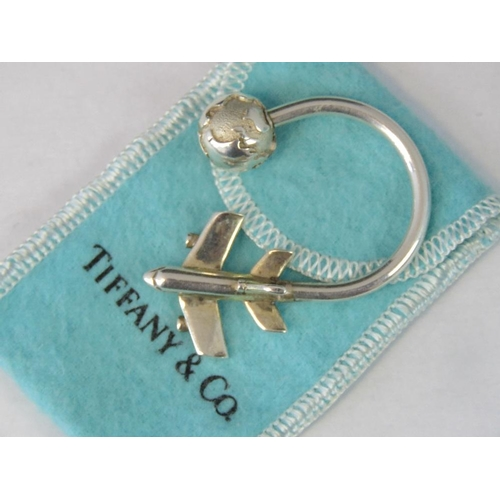 14 - A key fob with airplane and globe terminals stamped 925 Tiffany, with box and pouch....