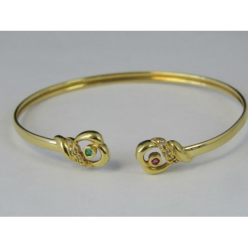 164 - An 18ct gold bangle with abstract heart shaped terminals one set with ruby and diamonds the other wi...