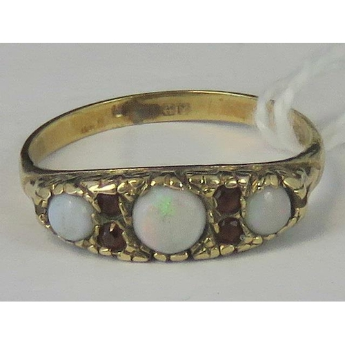 170 - A gold opal and ruby ring, three graduated opal cabachons separated by two pairs of rubies set in ye...