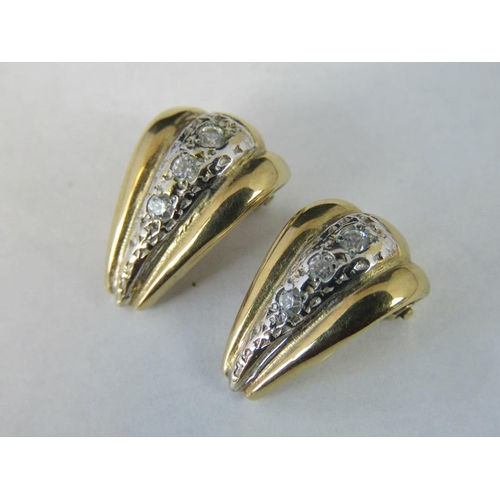 181 - A pair of 9ct gold and diamond clip on earrings, triangular form with white metal stripe set with th...