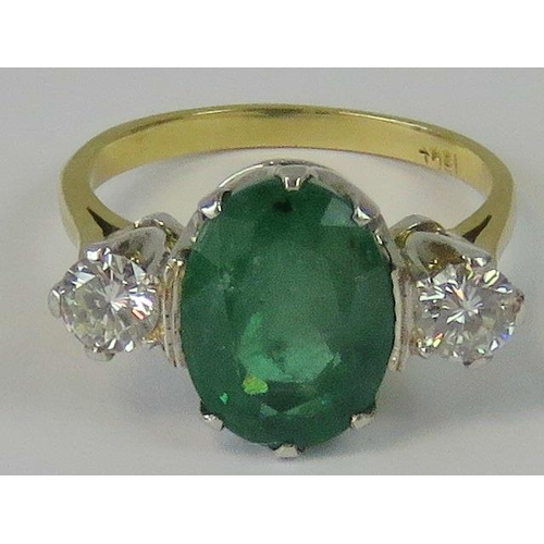 189 - A superb 18ct gold emerald and diamond ring. Huge central oval emerald approx 4.8cts, flanked on eit...