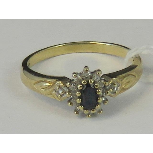 199 - A 9ct gold sapphire and diamond cluster ring, central oval sapphire surrounded by a gallery of diamo...