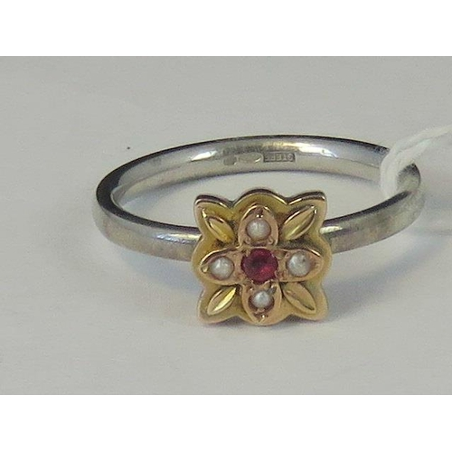 204 - A silver and yellow metal ring, yellow metal head set with ruby and four seed pearls on a white meta...