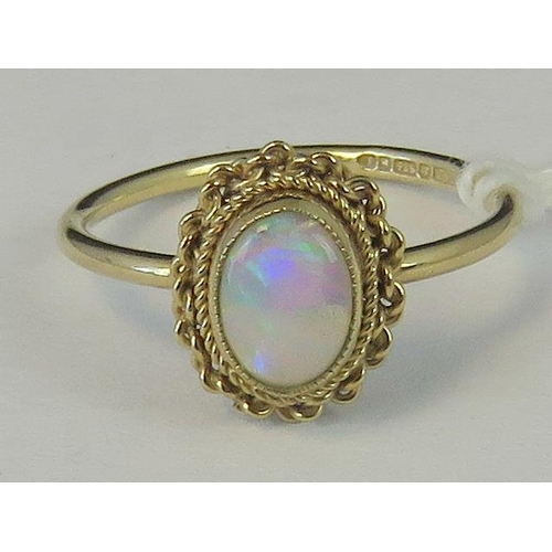 207 - A 9ct gold opal ring, oval cabachon in yellow metal twisted rope mount, hallmarked 375, size K - L, ...