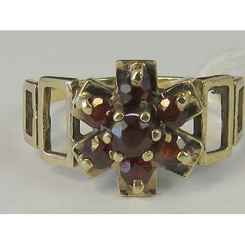 212 - A 9ct gold and garnet daisy cluster ring, open yellow metal graduated rectangle design shank, 9ct ha...