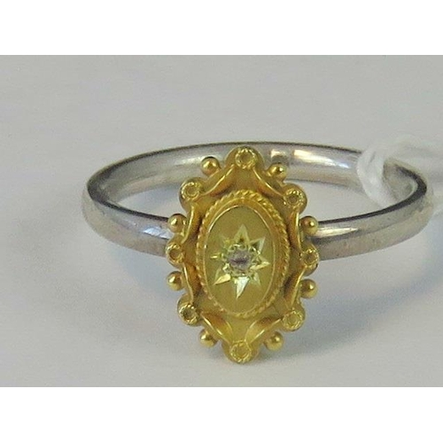 214 - A silver and yellow metal ring, yellow metal head set with diamond chip on a white metal shank hallm...