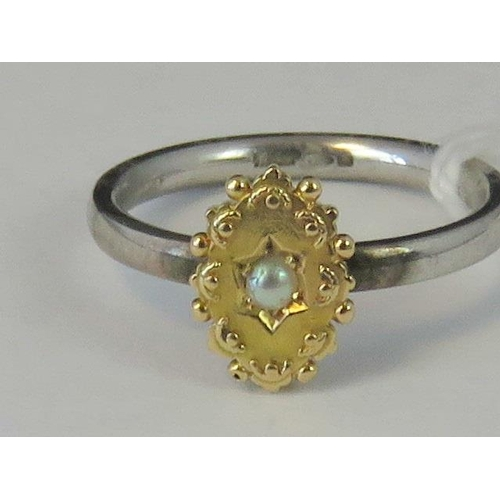 215 - A silver and yellow metal ring, yellow metal head set with seed pearl on a white metal shank hallmar...