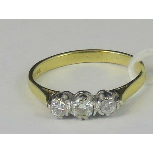 217 - An 18ct gold three stone diamond ring, three diamonds total 0.25cts set in white metal on a yellow m...