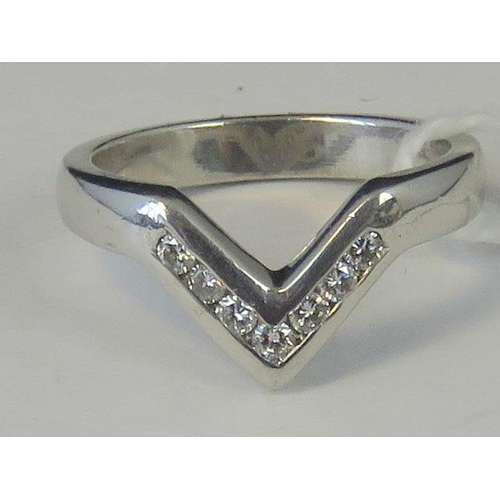 221 - A white metal and diamond wishbone style ring, seven channel set diamonds approx 0.28ct total, no ha...