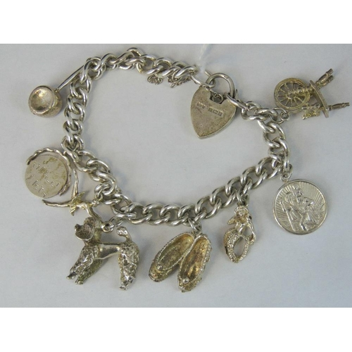 237 - A silver charm bracelet, hallmarked silver heart padlock, eight charms, 48.35g...