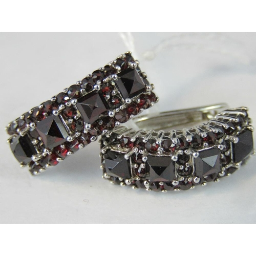 239 - A pair of silver and garnet half hoop earrings, four square cut garnets surrounded and separated by ...