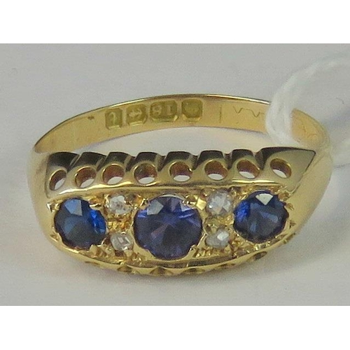 242 - An 18ct gold sapphire and diamond ring, three graduated Ceylon blue sapphires separated by two pairs...