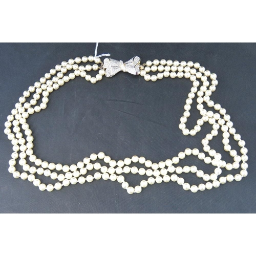 249 - A long triple strand faux pearl necklace with bow design clasp....