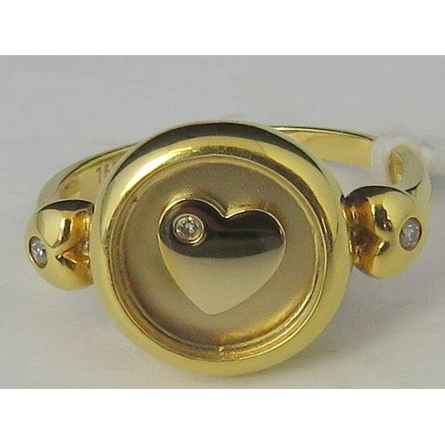 254 - An 18ct gold and diamond ring, central oval panel with spinning heart and hearts to shoulders each s...