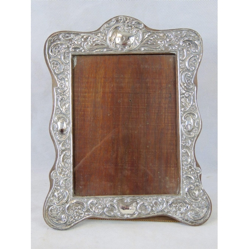 23 - A HM silver repoussse photo frame with four blank cartouches and floral pattern, wooden backing, 30 ...