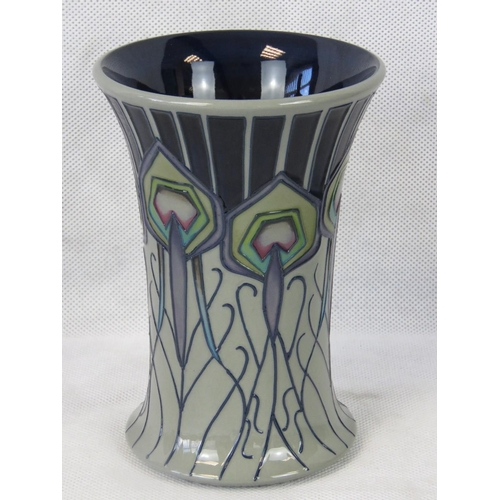 520 - A Moorcroft vase with Peacock Feather design, 16cm high, red dot to base....