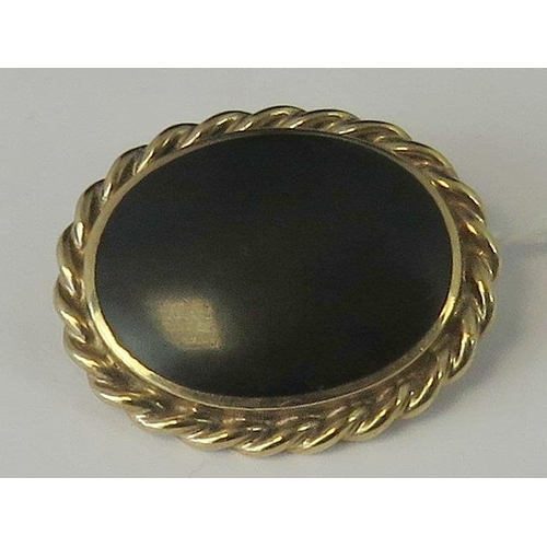 257 - A 9ct gold and onyx brooch, large oval onyx set in rope twist frame hallmarked 375 (1990's), 3.3cm w...