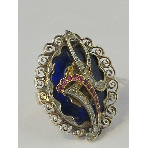 258 - A yellow metal, diamond and ruby ring. Central blue enamel panel surmounted by swirls of ruby and di...