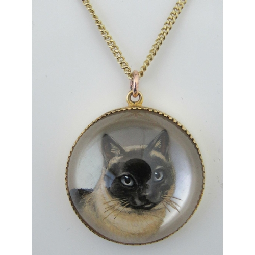 131 - A 9ct gold painted reversed crystal intaglio Siamese cat pendant made by  Ernest.M. Pradier (1881-19...