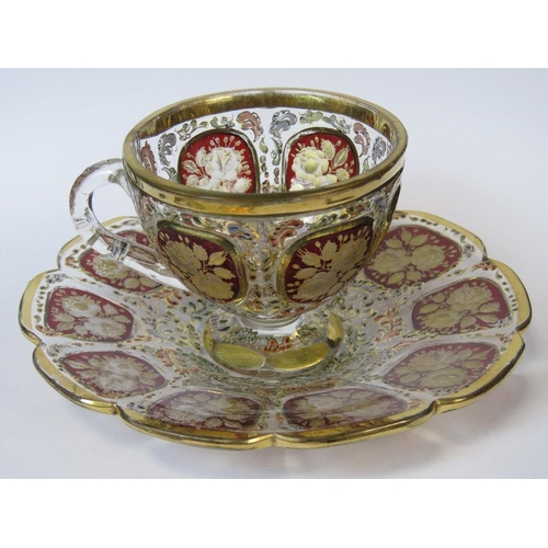 858 - A delightful Venetian style overlaid and gilded glass cup and saucer decorated with floral vignettes...