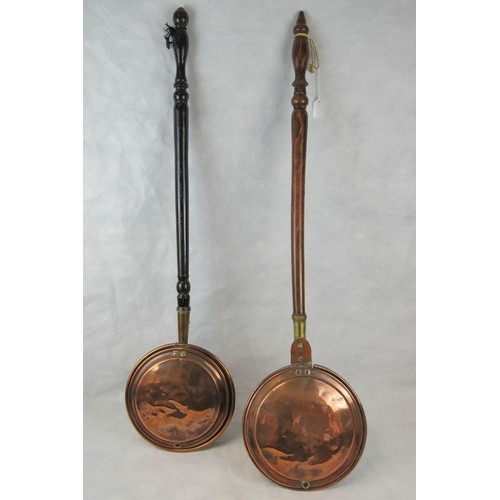 859 - Two 19thC copper warning pans each having a long, turned fruitwood handle....
