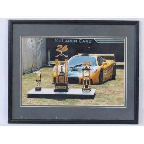 14 - A coloured photograph of a McLaren F1GTR 'Harrods', signed verso by Derek Bell, Justin Bell and Andy...