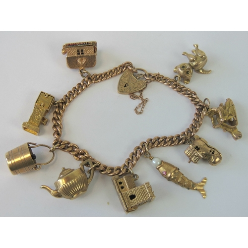 25adafd40ab2b A 9ct gold charm bracelet with heart padlock clasp and nine charms ...