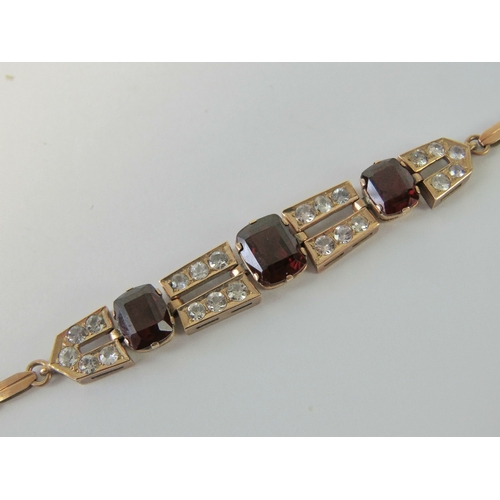 100 - A delightful Edwardian white sapphire and garnet bracelet, three graduated cushion cut garnets (appr...