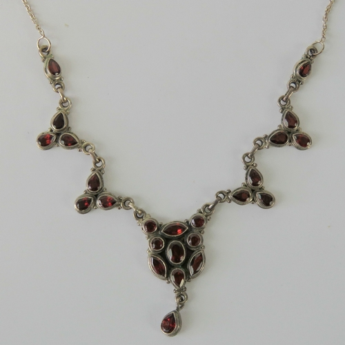 103 - A silver and garnet necklace seven panels encrusted with various faceted cuts of garnet in rubover s...