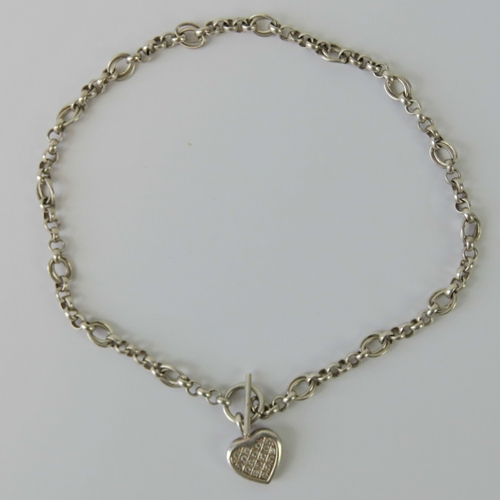 106 - A heavy HM silver fancy link chain having T-bar clasp and white stone encrusted heart shaped pendant...