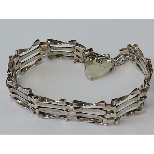 112 - A HM silver gate link bracelet having four bars and complete with HM silver heart padlock clasp, bra...