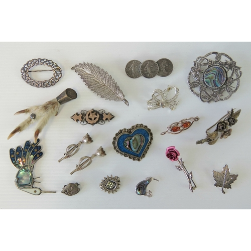 121 - A quantity of silver and white metal brooches including; sterling filigree leaf, sterling filigree b...