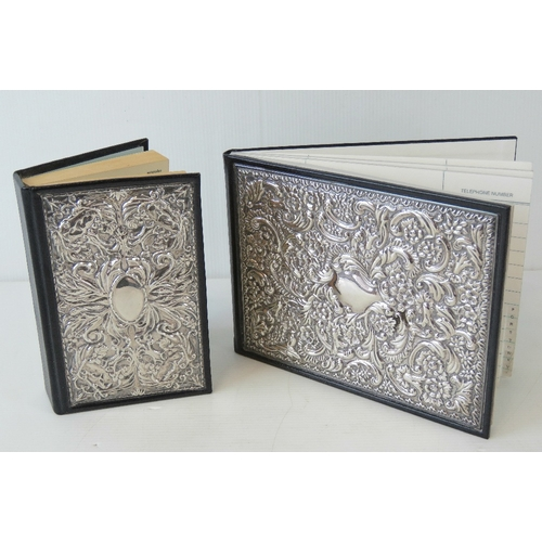 2 - A HM silver and leather bound address book with matching dictionary, each having floral repoussé pan...