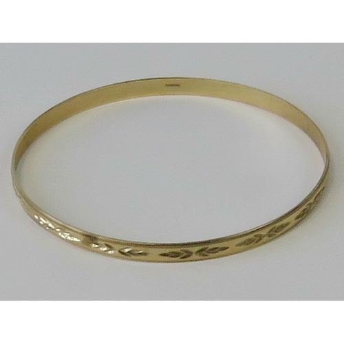 101 - A 9ct yellow gold bangle having engraved pattern throughout, hallmarked 375, 6.8cm dia, 7.2g....