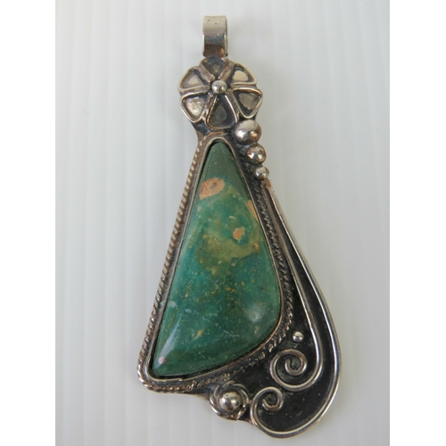126 - A hand made pendant having triangular green agate in floral white metal setting, 7cm in length....