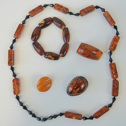 127 - Two vintage Baltic amber brooches together with an 'egg yolk' amber type brooch, a bracelet and a vi...