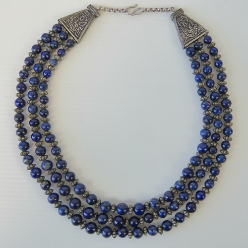 109 - A lapis lazuli necklace comprising three graduated strands of lapis lazuli beads with white metal sp...