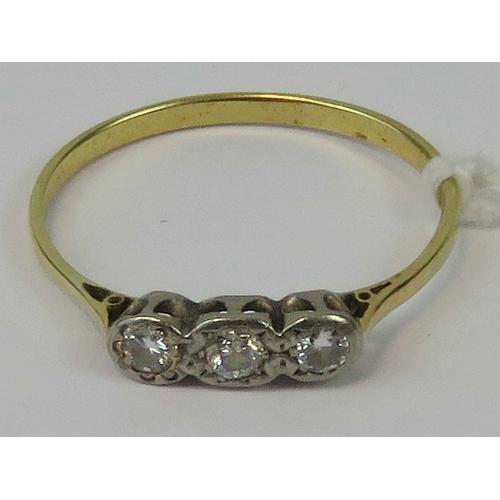 105 - A three stone diamond ring, graduated round cut brilliant diamonds illusion set in white metal, appr...