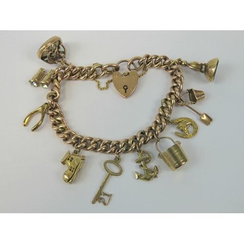 113 - A 9ct rose gold heavy curb link charm bracelet having heart padlock clasp, four 375 hallmarked charm...