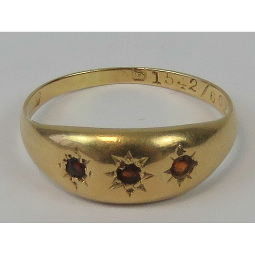 130 - A yellow metal and garnet gypsy ring having three graduated garnets in star settings, hallmark indis...