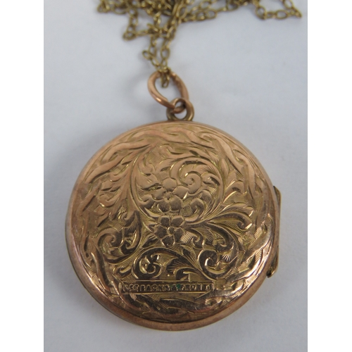 137 - A 9ct rose gold plated locket of circular form having floral engraving and opening to reveal photo o...