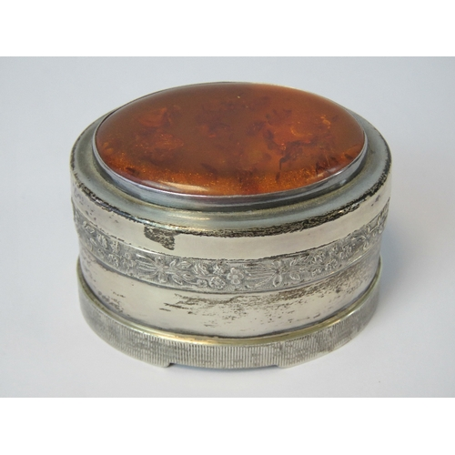 12 - A HM silver trinket box having large oval Baltic amber cabachon to lid and raised floral bouquet pat...