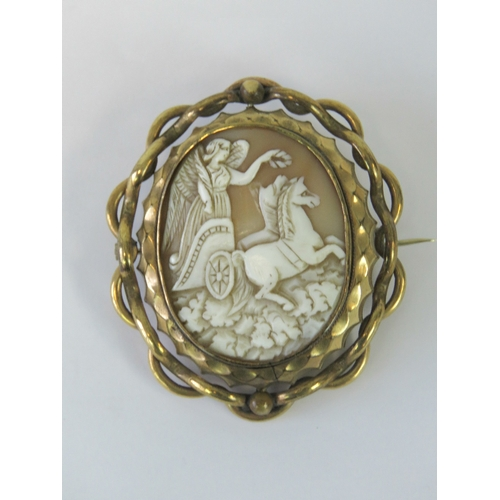 110 - A large Victorian carved shell cameo brooch having Classical female upon chariot to central spinning...