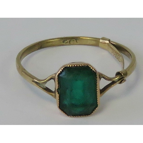 133 - A 9ct gold ring having octagonal faceted green paste, stamped 9ct and having 9ct gold ring resizer a...