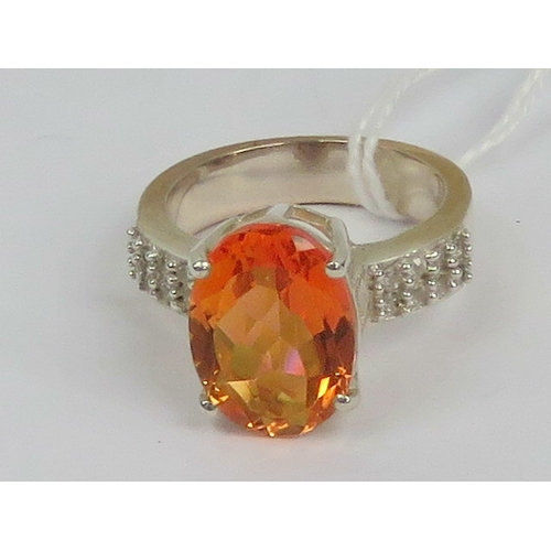 c2a50053dd1fb A silver cocktail ring having large oval faceted orange stone and ...